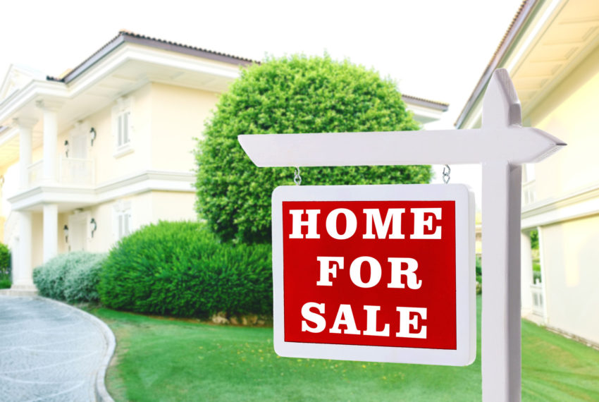 'Home For Sale' sign in front of a yellow house with shrubs.