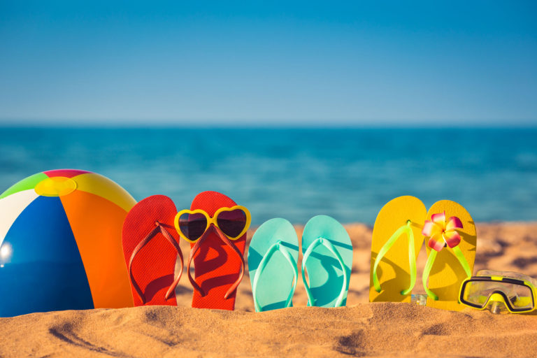 Three pairs of flipflops, sunglasses, and a beachball sit on the beach.